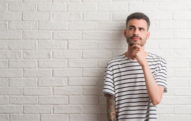 Young adult man standing over white brick wall serious face thinking about question, very confused idea