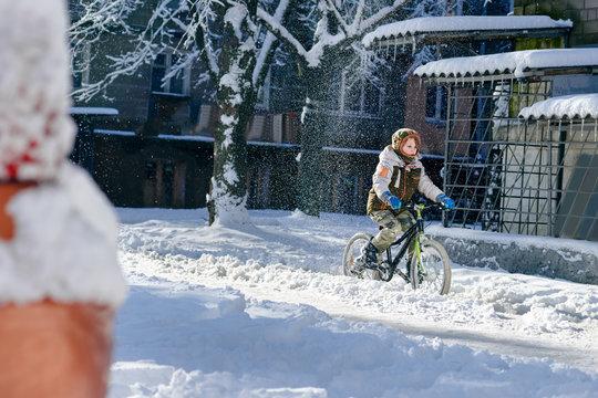 Young boy riding bike in beautiful winter city