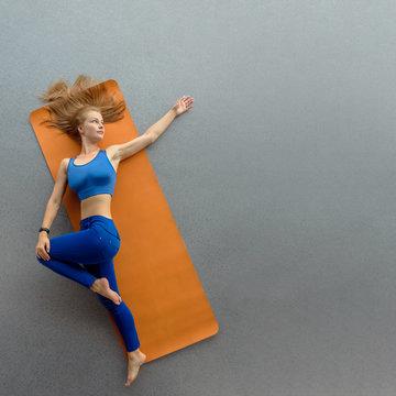 Top view of flexible slim woman exercising on yoga mat