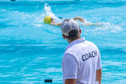 Male swimming coach watching his swimmer practice