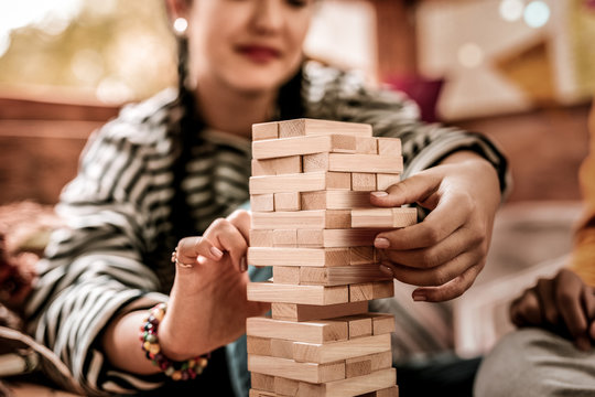 So careful. Attentive brunette girl keeping smile on face while playing jenga