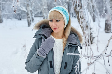 Beautiful girl with long curly hair and white clothes having fun outdoor in winter forest under snowflakes.