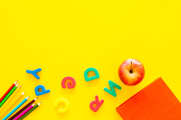 Primary school concept. Letters of english alphabet, apple and color pencils on yellow background top view space for text