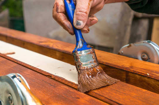 Painter with paintbrush painting wooden surface