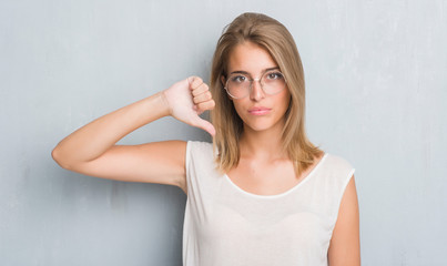 Beautiful young woman standing over grunge grey wall wearing glasses with angry face, negative sign showing dislike with thumbs down, rejection concept