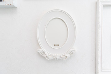empty vintage retro old oval white picture frame on wall.