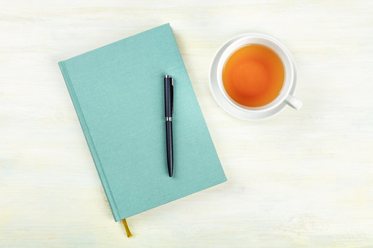A teal blue journal with a pen and a cup of tea, shot from above, an elegant notebook on a light background with a place for text