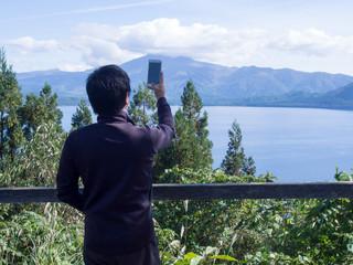 スマートホンで風景を撮影する男性 田沢湖