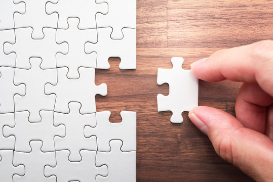 Putting last jigsaw puzzle piece. Solving and completing the task. The correct solution. Assembling white jigsaw puzzle pieces.