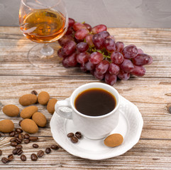 Black coffie and glass with brandy served with grape and chocolate