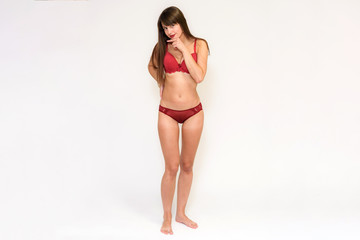 Studio photo of a beautiful brunette girl on a white background in a bathing suit.