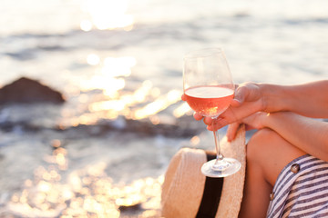 Girl is sitting on sea beach with wineglass of wine at sunset in summer vacation in resort. Tourist woman in striped dress with straw hat is enjoying life, relaxing, drinking, traveling. Wall mural