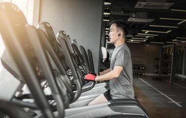 man in sportswear running on treadmill at gym