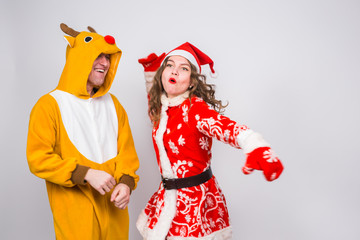 Holiday, Christmas and fun concept - Funny couple in deer costume and Santa Claus clothes are dancing on white background
