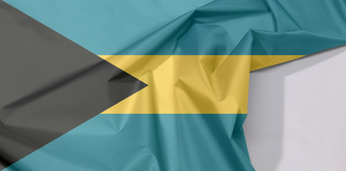Bahamas fabric flag crepe and crease with white space, triband of aquamarine (top and bottom) and gold with the black chevron aligned to the hoist-side.