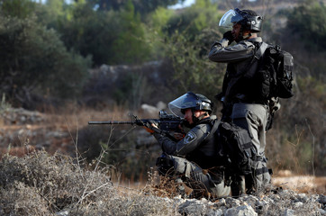 Israeli border policeman aims his weapon during clashes over an Israeli order to shut down a Palestinian school near Nablus in the occupied West Bank