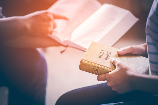 Male adults are reading the Holy bible by pointing to the character and to share the gospel to youth. The cross symbol, glow over the books of the Bible, Concepts of Christianity.