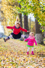 Two cute girls have fun outdoor. Two sisters are in the autumn park.