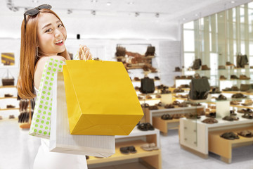 Smiling asian woman carrying shopping bags on store