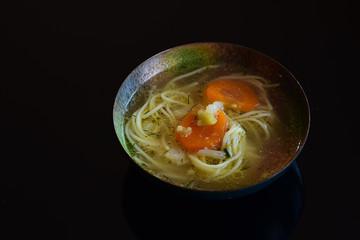 Broth, warm soup on black.