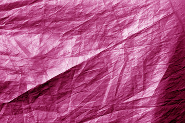 Crumpled plastic textile texture in pink color.