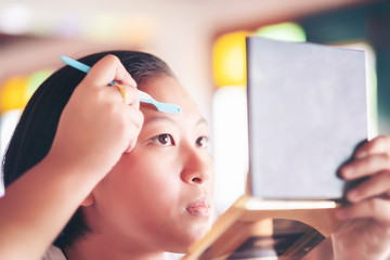 lady shave Brow. young attractive asian woman beauty image, makeup artist used eyebrow razor makeup a pretty woman face