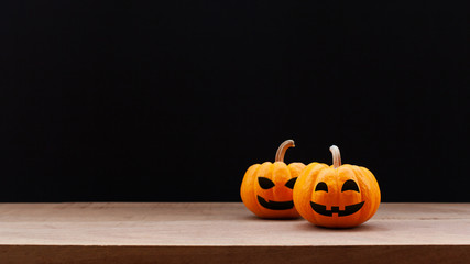Pumpkin on wood table with dark background. Halloween and decoration concept. Front view and copy space
