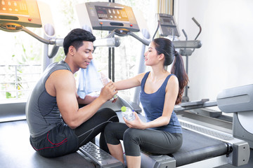 Attractive young fitness couple resting on Threadmill in the gym, Young couple relaxing and drinking water after training.