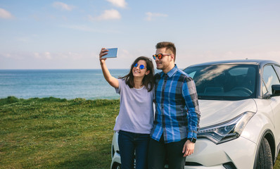 Young couple doing a selfie leaning on the car near the coast