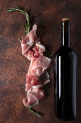 Fototapete - Prosciutto with rosemary and bottle of red wine.