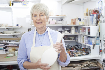 Portrait Of Senior Woman Holding Vase In Pottery Studio