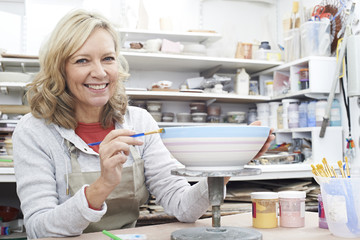 Portrait Of Mature Woman Decorating Bowl In Pottery Class