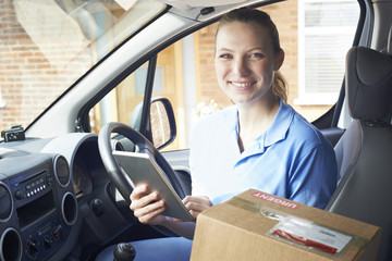 Portrait Of Female Courier In Van With Digital Tablet Delivering Package To Domestic House