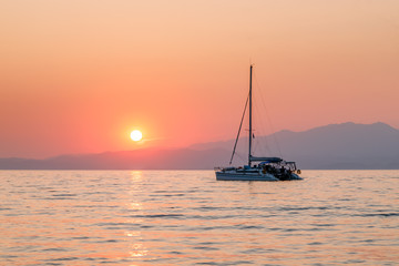 Yacht in the sea at sunset. Beautiful orange sunset colors, mountains in the background. Calm and tranquility. Holidays in Greece.