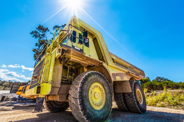 Enormous green dumper truck under sun flare