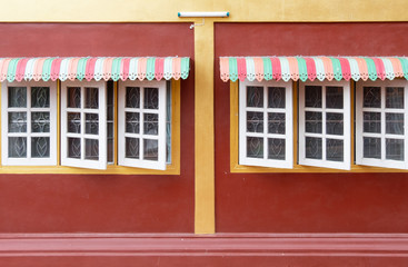Colorful metal canopy on the wooden window.