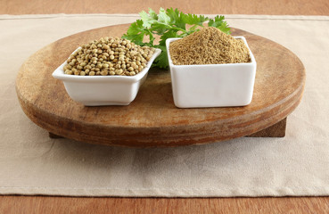 Coriander powder, with coriander seeds and leaves, which is a cooking ingredient, on a wooden table