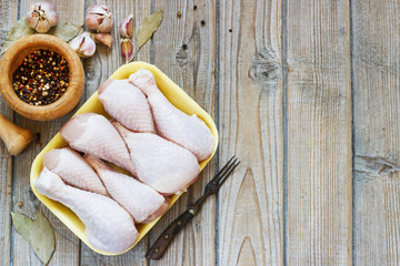 Bowl with raw chicken legs on wooden background, top view