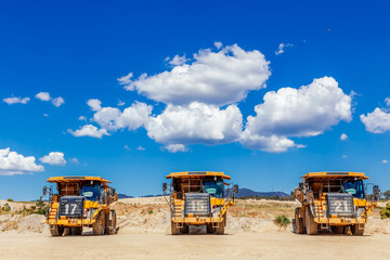 Three big dumper trucks in a row under blue sky with beautiful clouds