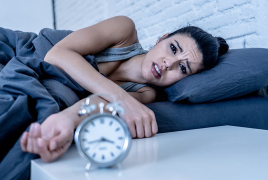 Attractive woman staring at alarm clock trying to sleep feeling stressed depressed and sleepless