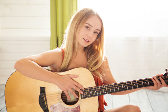 Girl playing guitar and singing. Young woman with long hair studying music at home. Woman sitting on floor and plays acoustic guitar and sing alone at home