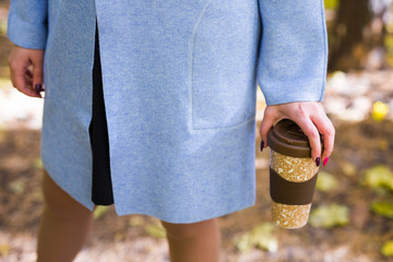 Close up of woman holding a cup of takeaway coffee cup on autumn street