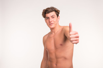 People, gesture, fitness and sport concept - athletic shirtless man showing thumb up over white background