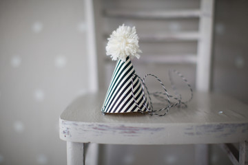 Clown hat with black and white stripes and white pompon on a chair