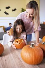 Girl carving pumpkin for Halloween