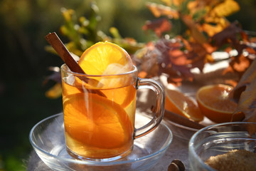 Foto auf AluDibond Tee hot tea drink with orange slices and cinnamon in a glass cup in backlit in the autumn garden, selected focus, narrow depth of field