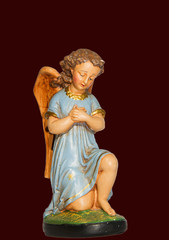 Angel in prayer with blue dress, gypsum, statue made of gypsum and hand painted, isolated on dark red background