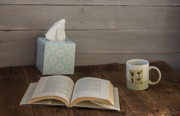 a cup with cafe an open book and a box with napkins