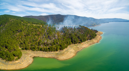 Aerial panorama of forest fire on shores of Blowering Reservoir, NSW, Australia