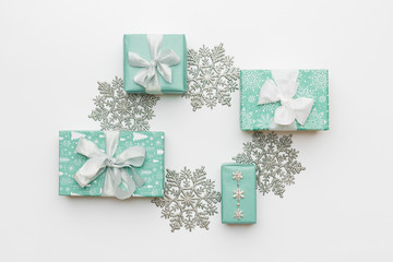 Beautiful christmas gifts and silver snowflakes isolated on white background. Turquoise colored wrapped xmas boxes. Gift wrapping concept.